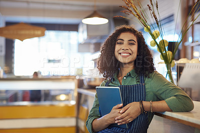 Buy stock photo Portrait of a young woman holding a digital tablet while working in a cafe