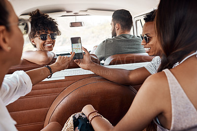 Buy stock photo Shot of a group of young friends using gps on a smartphone during a road trip