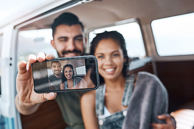 Buy stock photo Shot of a happy young couple taking selfies on a road trip