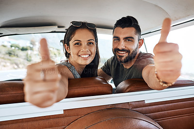 Buy stock photo Shot of a young couple giving a thumbs up on a road trip