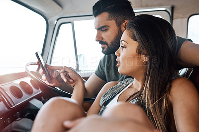 Buy stock photo Shot of a young couple using using a smartphone during a road trip