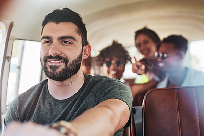 Buy stock photo Shot of a handsome young man taking his friends on a road trip