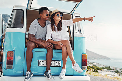 Buy stock photo Shot of a happy young couple taking a break while out on a road trip