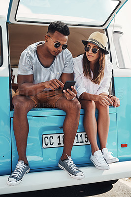 Buy stock photo Shot of a young man showing his girlfriend something on his cellphone while sitting together outside