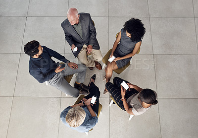 Buy stock photo High angle shot of a diverse group of  businesspeople using smartphones while sitting together in a modern office