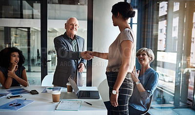 Buy stock photo Cropped shot of a mature businessman shaking hands with a businesswoman during a meeting in a boardroom
