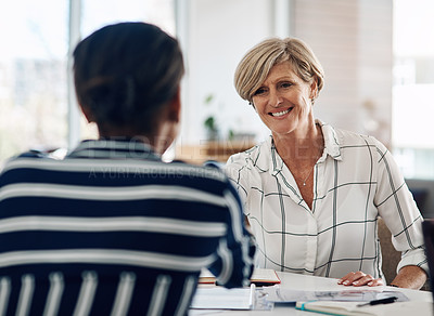 Buy stock photo Cropped shot of two businesswomen shaking hands during a meeting in a modern office