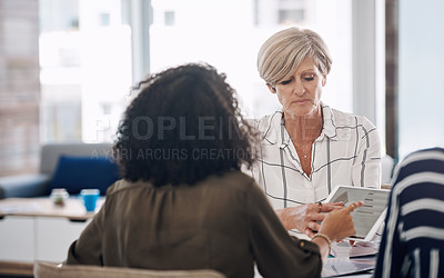 Buy stock photo Cropped shot of two businesswomen using a digital tablet during a meeting in a modern office