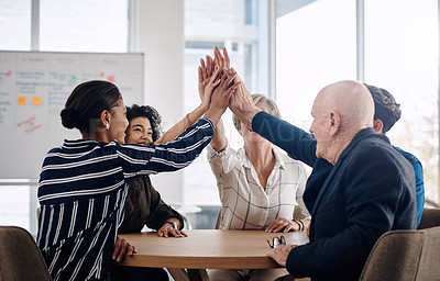 Buy stock photo Cropped shot of a diverse group of businesspeople joining their hands together in unity while sitting in a modern office