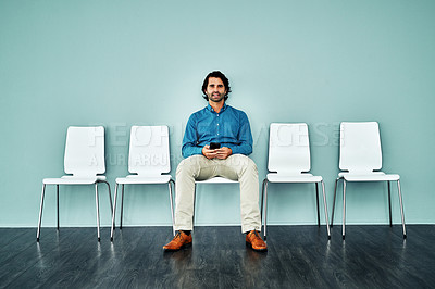Buy stock photo Studio shot of a young businessman using a smartphone while waiting in line against a blue background