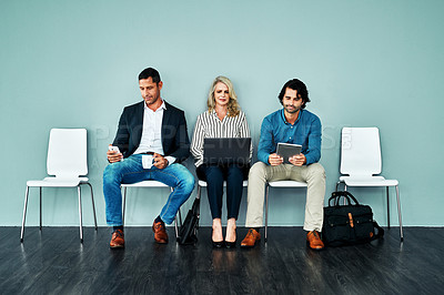Buy stock photo Studio shot of a group of businesspeople using their wireless devices while waiting in line against a blue background