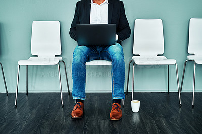 Buy stock photo Studio shot of a businessman using a laptop while waiting in line against a blue background