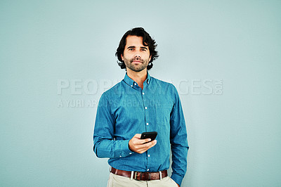 Buy stock photo Studio shot of a young businessman using a smartphone against a blue background