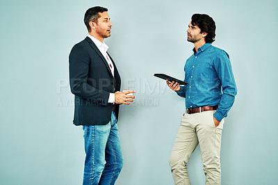 Buy stock photo Studio shot of two businessmen having a discussion against a blue background