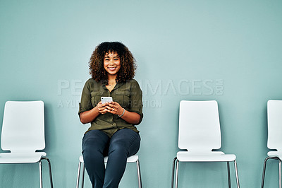 Buy stock photo Studio shot of a young businesswoman using a smartphone while waiting in line against a blue background