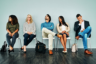 Buy stock photo Studio shot of a group of businesspeople looking bored while waiting in line against a blue background