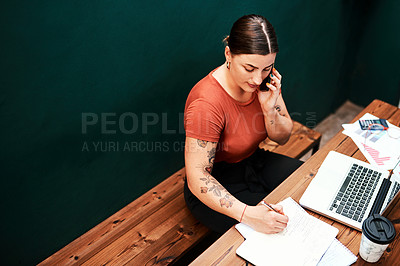 Buy stock photo Cropped shot of an attractive young businesswoman sitting alone and using her cellphone while writing in her notebook