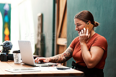 Buy stock photo Cropped shot of an attractive young businesswoman sitting alone and using her cellphone while using her laptop