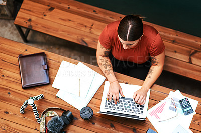 Buy stock photo High angle shot of an attractive young businesswoman sitting alone and blogging on her laptop