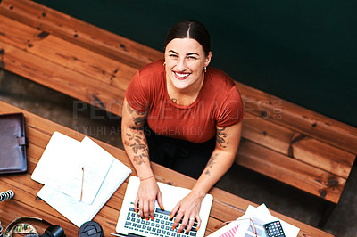 Buy stock photo High angle portrait of an attractive young businesswoman sitting alone and blogging on her laptop