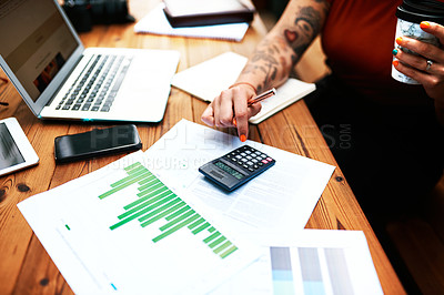 Buy stock photo Cropped shot of an unrecognizable businesswoman sitting and using a calculator to calculate her finances