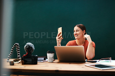 Buy stock photo Cropped shot of an attractive young businesswoman sitting alone against a green background and using her cellphone to take selfies
