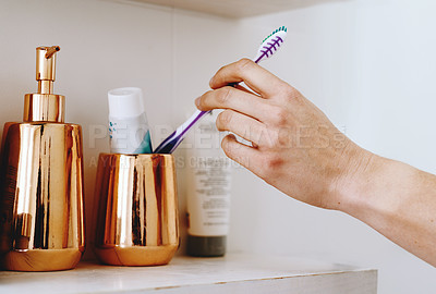 Buy stock photo Cropped shot of of an unrecognizable woman taking out a toothbrush from her bathroom cabinet