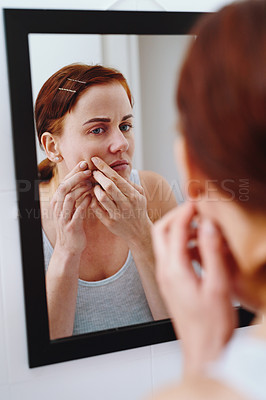 Buy stock photo Shot of an attractive young woman looking in the mirror and popping a pimple on her face at home