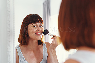 Buy stock photo Shot of an attractive young woman applying makeup on her face inside her bathroom at home