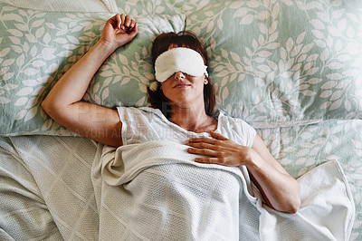 Buy stock photo Shot of an attractive young woman sleeping with a sleep mask on in her bed at home