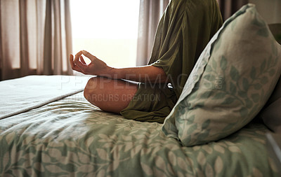 Buy stock photo Cropped shot of an unrecognizable young woman meditating while sitting on her bed at home