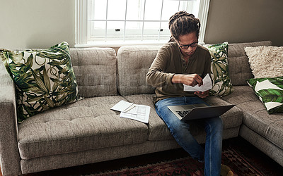 Buy stock photo Shot of a focused young man working on a laptop and doing paperwork while being seated on a sofa at home during the day