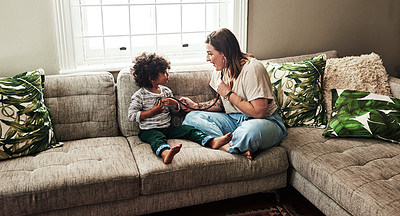 Buy stock photo Shot of a cheerful young woman and her son playing around with a stethoscope while being seated on a sofa at home during the day