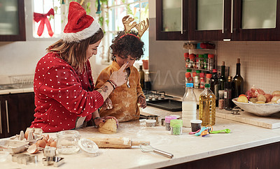 Buy stock photo Cropped shot of a cheerful young woman and her son baking cookies together in the kitchen during christmas time at home