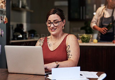 Buy stock photo Cropped shot of a cheerful young woman working on a laptop and doing paperwork while being seated at a table at home