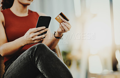 Buy stock photo Shot of an unrecognizable designer holding a credit card while using her cellphone