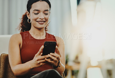 Buy stock photo Cropped shot of a beautiful young designer using her cellphone in her office