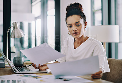 Buy stock photo Shot of a young businesswoman going through paperwork while working in her home office