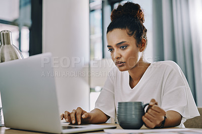 Buy stock photo Shot of a young businesswoman using a laptop and having coffee while working in her home office