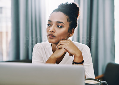 Buy stock photo Shot of a young businesswoman looking thoughtful while using a laptop in her home office