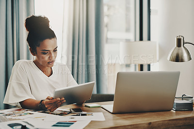 Buy stock photo Shot of a young businesswoman using a digital tablet and laptop while working in her home office