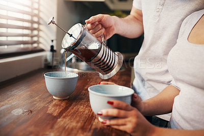 Buy stock photo Cropped shot of an unrecognizable couple pouring their morning coffee
