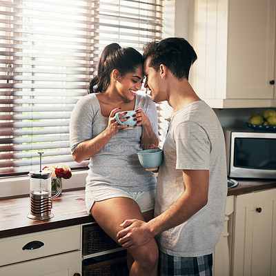 Buy stock photo Shot of a young couple having coffee in their kitchen at home