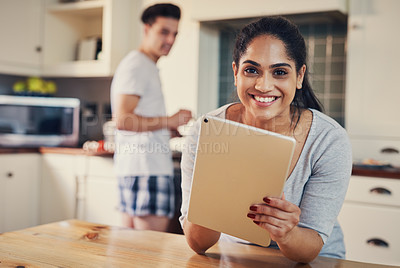 Buy stock photo Shot of a young woman using a digital tablet while her boyfriend stands in the background