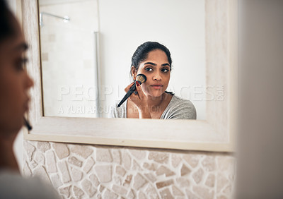 Buy stock photo Cropped shot of a young woman applying makeup while looking into her bathroom mirror