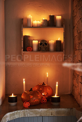 Buy stock photo Still life shot of carved pumpkins and lit candles placed together in celebration of halloween