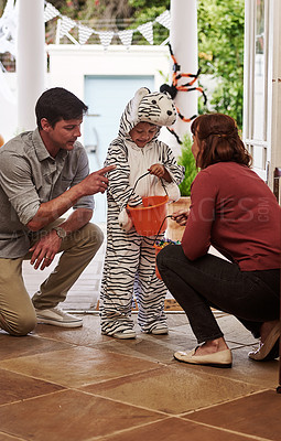 Buy stock photo Shot of an adorable little boy celebrating halloween with his parents at home
