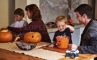 Buy stock photo Shot of an adorable young family carving out pumpkins and celebrating halloween together at home