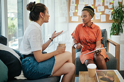 Buy stock photo Cropped shot of two attractive young businesswomen sitting together and having a discussion in the office