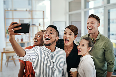 Buy stock photo Cropped shot of a diverse group of businesspeople standing together and taking a selfie with a cellphone in the office